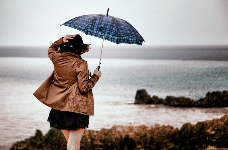 Autumn Rain Rainy Days Beauty In Nature Day Fall Full Length Girl Horizon Over Water Leisure Activity Lifestyles Men Nature One Person Outdoors People Real People Rear View Sea Skirt Sky Standing Umbrella Water Women