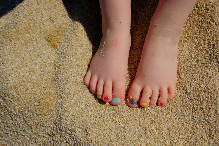 Low Section Of Girl With Colorful Nail Polish On Sand At Beach
