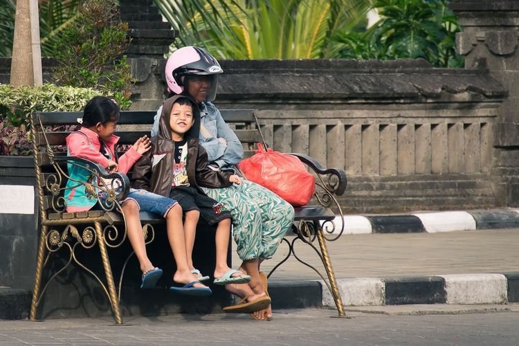 Feel The Journey Waiting Family Children Smile Cheeky Play Playing Journey Bus Stop Sitting On A Bench Outdoors City Bali Happy Togetherness Closeness Traveling Travel Travel Photography