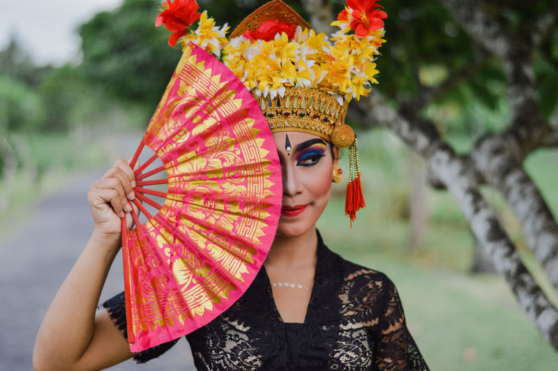 Close-up of young woman wearing headdress while holding folding fan against trees