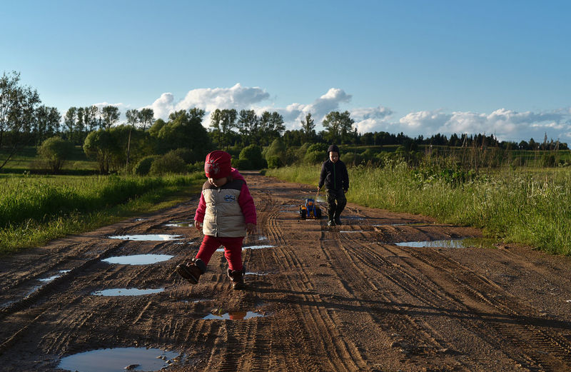 Two children playing on dirt road