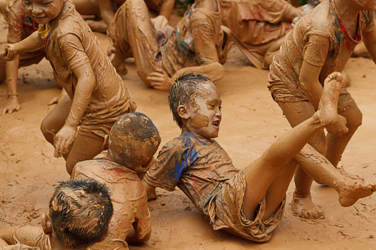 Unidentified Children's Group In Northern Village Is Playing On Clay Merrily In Chiang Mai, Thailand. Children Volunteer Child Childhood Day Dirt Full Length Group Of People High Angle View Mud People Real People Sitting Togetherness Friend Kid Clay Dirty Ancient Civilization Children Muddy Soil