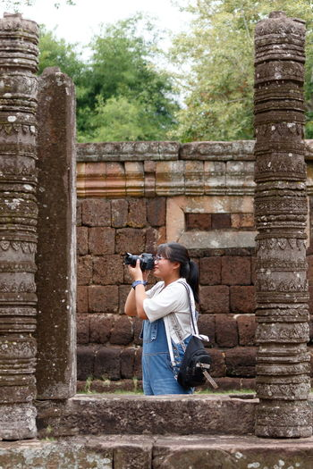 Girl photographing through camera against wall
