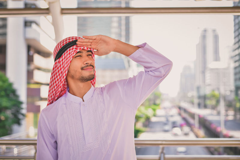 Smiling young man shielding eyes while standing on elevated road