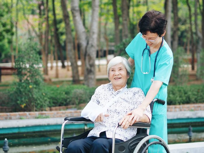 Nurse With Female Patient On Wheelchair At Park