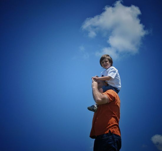 Low angle view of father carrying happy son on shoulders against blue sky