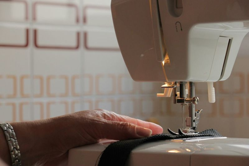 Cropped Hand Of Woman Sewing Textile On Machine