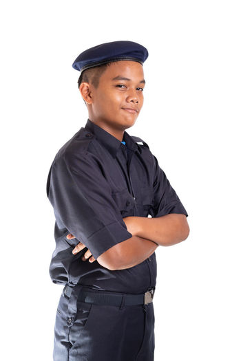 Young Asian man in police uniform isolated on white background. White Background Studio Shot Cut Out One Person Clothing Looking At Camera Standing Young Adult Cap Portrait Men Police Officer Security Face Smile Service Occupation Confidence  Three Quarter Length Indoors  Hat Uniform Young Men Arms Crossed