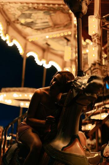 Man sitting in illuminated carousel at amusement park