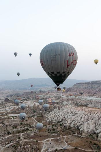 Hot air balloon flying over rocks