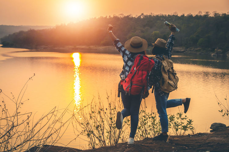 Two People Nature Sunset Sky Beauty In Nature Outdoors Landscape Travel Backpack Backpacker Women Sunlight Leisure Activity Real People Water Standing Hat Adult