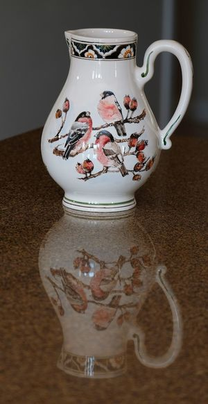 Light cream coloured jug with pink birds on branches with reflection on table Reflection Art And Craft Birds Ceramics Close-up Container Crockery Drink Floral Pattern Food And Drink Indoors  Jug No People Pattern Pink Birds Porcelain  Refreshment Still Life