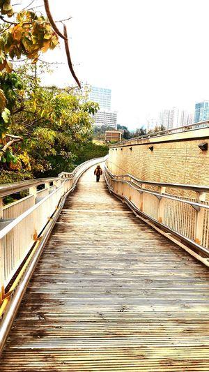 Man on footbridge in city against sky