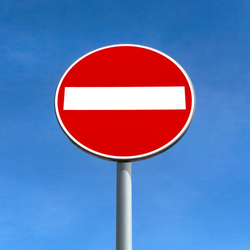 Close-up of road sign against clear blue sky