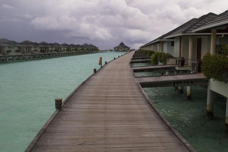 Wooden pier amidst buildings against sky