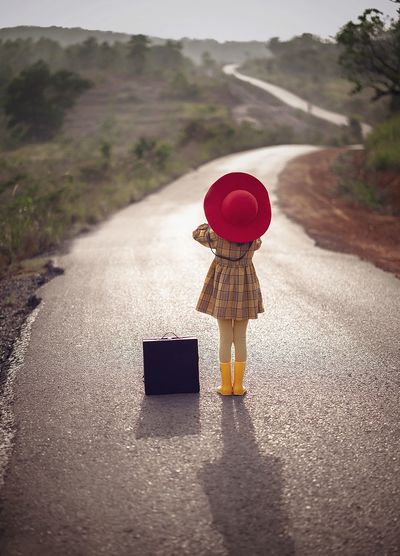 Rear view of girl with suitcase standing on road