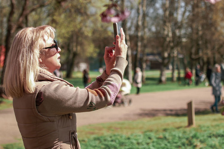 Side view of woman holding smart phone
