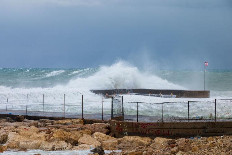 Waves breaking on rocks against sky