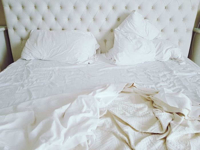 Crumpled blanket with pillows on bed