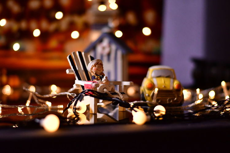 Close-up of toys with illuminated string lights on table at home