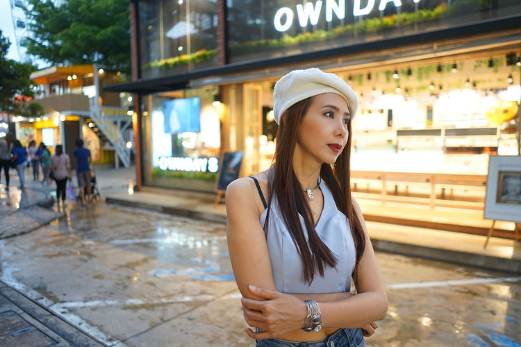 Woman looking away while standing in illuminated city