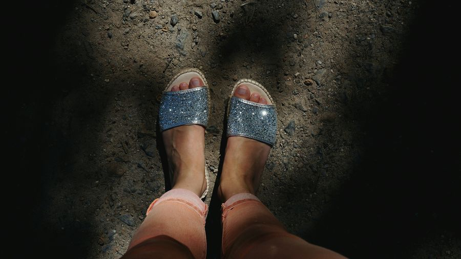 Low section of woman wearing sparkling sandals