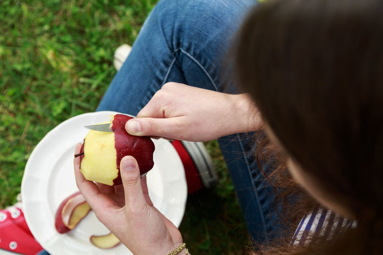Midsection of woman holding apple