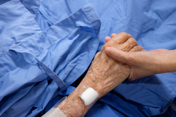 Cropped image of female doctor holding patient hand on bed