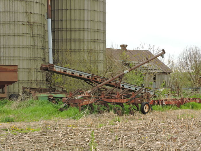 Farm Equipments Field Grass Day Nature Architecture Plant Abandoned No People Sky Land Built Structure Building Exterior Agricultural Machinery Agriculture Rusty Machinery Transportation Outdoors Clear Sky Obsolete Wheel