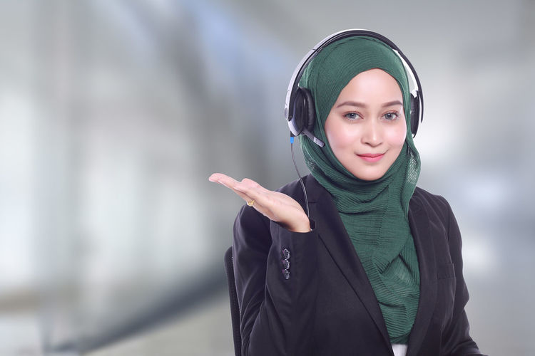 Portrait of confident businesswoman with headphones wearing hijab at call center