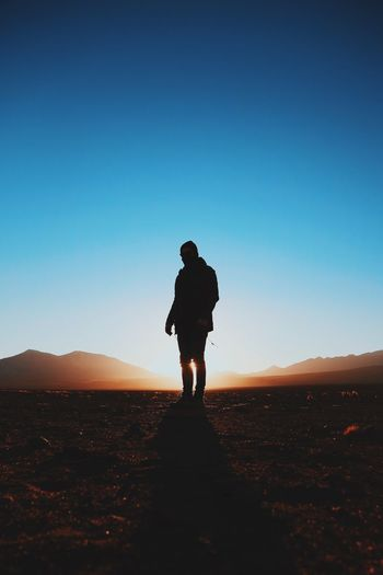 Man standing on landscape against clear sky