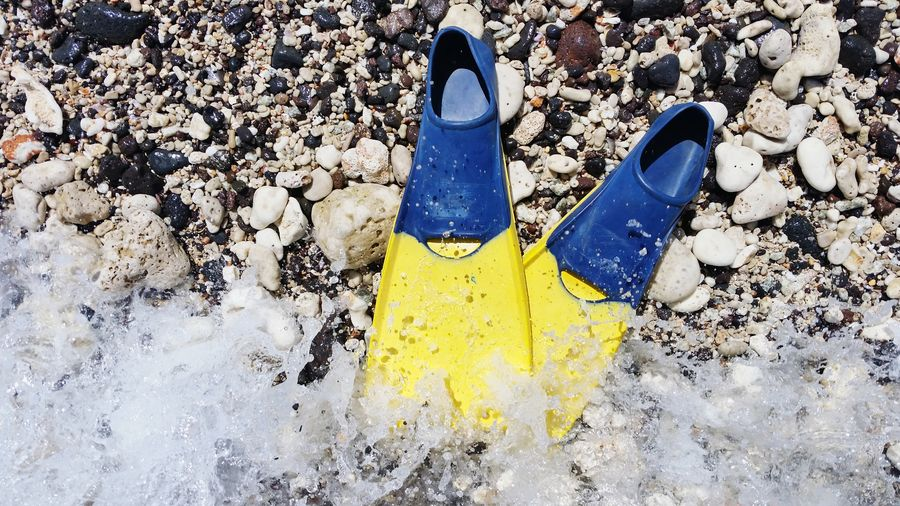 Yellow and blue swim fins about to be splashed by the surf on a rocky Hawaiian beach Overhead View Fins Bright Colors Active Recreation  Swimmer Swimming Getting Wet Snorkeling Swimwear Seashore Island Hawaii Big Island Tropics Tropical Summertime Waves Water Wet Splash Spray Droplets Beach Yellow High Angle View Close-up Footwear Things That Go Together Pair The Mobile Photographer - 2019 EyeEm Awards The Great Outdoors - 2019 EyeEm Awards My Best Photo The Minimalist - 2019 EyeEm Awards