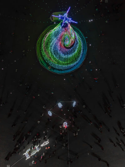 The main New Year tree in Minsk, Belarus Illuminated Arts Culture And Entertainment Night Multi Colored Architecture Celebration Decoration Amusement Park Built Structure Hanging Low Angle View No People Outdoors Disco Ball Building Exterior City Motion Minsk Belarus Christmas Christmas Decoration christmas tree Aerial View