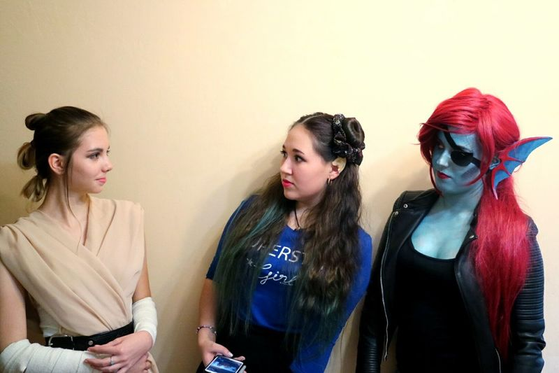 Female Friends In Costume Talking While Standing Against Wall