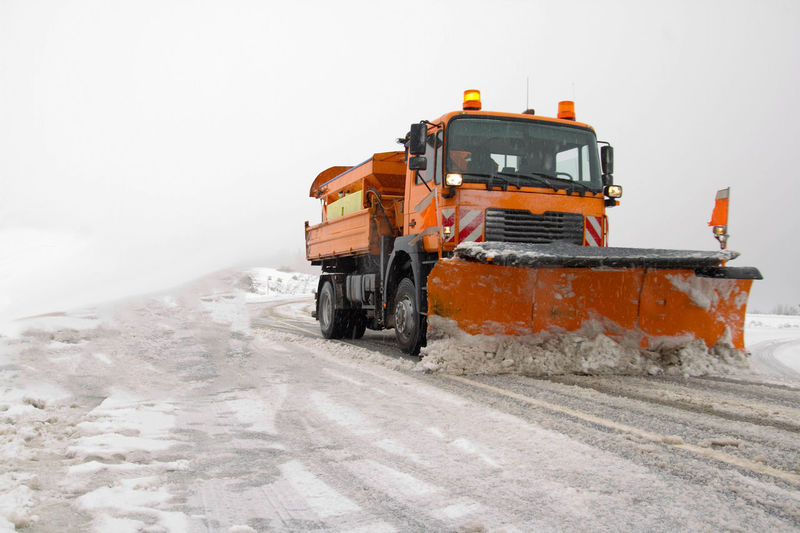 Construction vehicle cleaning snow on road