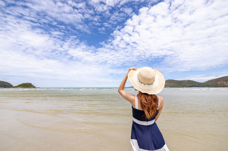 Rear view of woman wearing hat standing on beach