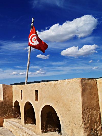 Tunisian Flag - Hammamet, Tunisia Historical Building Fortress Fortress Wall Kasbah Hammamet Tunisia Tunisie North Africa Maghreb Flag Tunisian Flag Kasbah Wall Islamic Architecture Blue Sky Architecture Urban Photography Travel Destinations Travel Tourism Tourist Destination Tourist Attraction