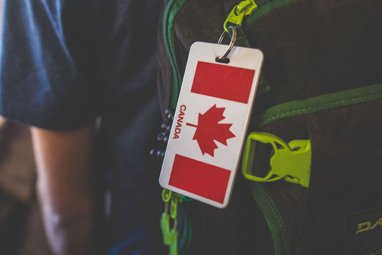 Close-up of canadian flag key ring hanging on man bag