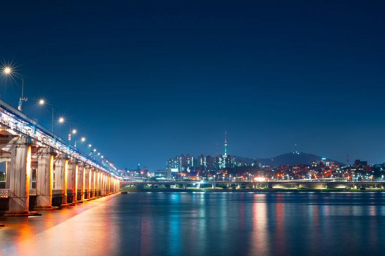 Illuminated bridge over river by buildings against sky at night in korea name banpo bridge