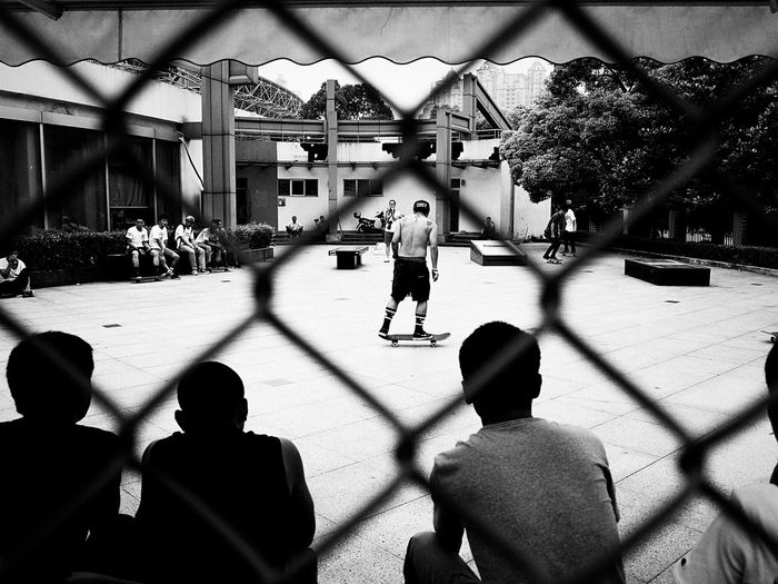 Group of people playing on chainlink fence
