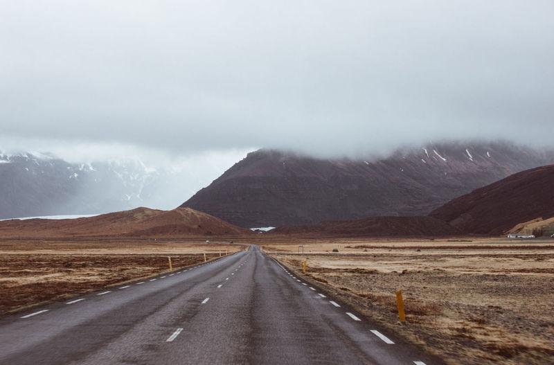 Empty road along mountain range against sky
