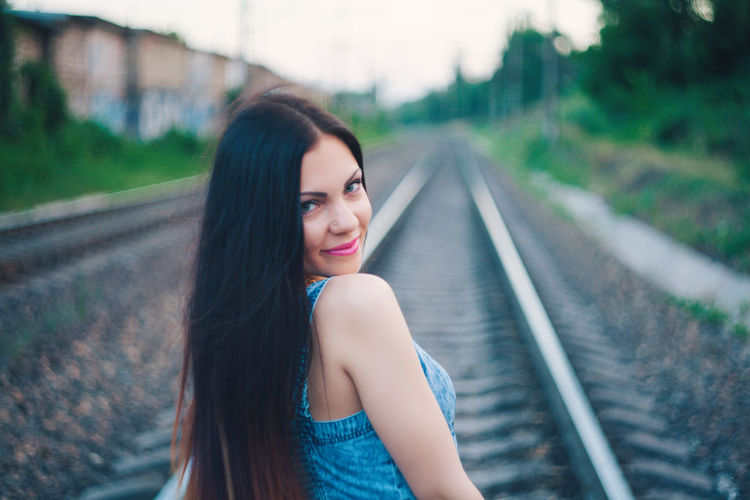 Young woman on railroad tracks