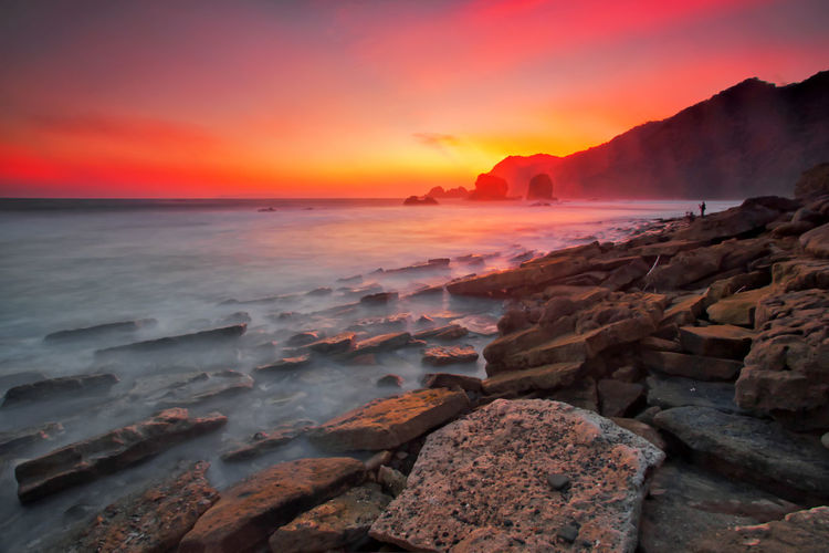 Majestic moment at Papuma beach,Indonesia Sea Sky Water Sunset Rock Solid Scenics - Nature Rock - Object Beauty In Nature Nature Cloud - Sky No People Land Motion Tranquility Horizon Horizon Over Water Orange Color Beach Power In Nature