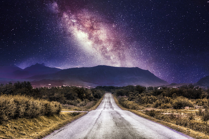 Scenic view of road against milky way sky at night