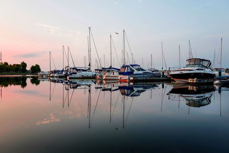 Serene Serenity Calm Mirror Effect Mirror Reflection Natural Beauty Sunrise And Clouds Sunrise Water Reflections Waterfront Symmetrical Reflection Water Sky Nautical Vessel Transportation Mode Of Transportation Waterfront Nature Mast Tranquility Sailboat Pole Harbor Beauty In Nature Scenics - Nature Lake Symmetry Moored