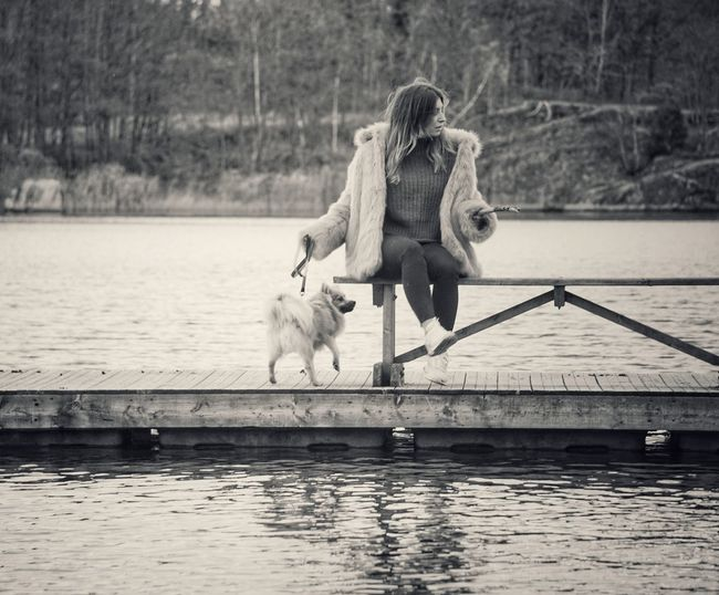 Woman with dog sitting on railing over lake