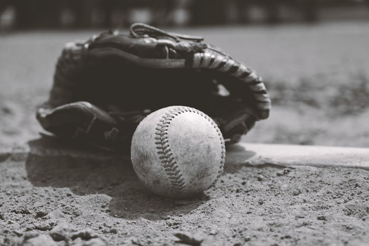 Close-up of baseball in glove on field