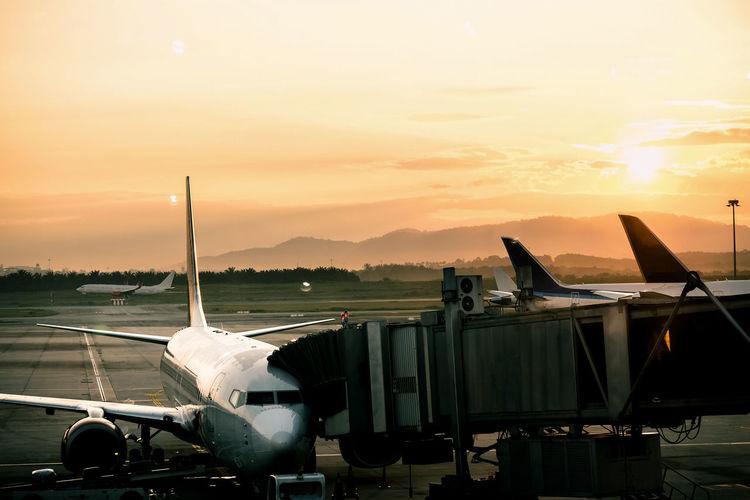 Airplane with passenger boarding bridge at airport against orange sky
