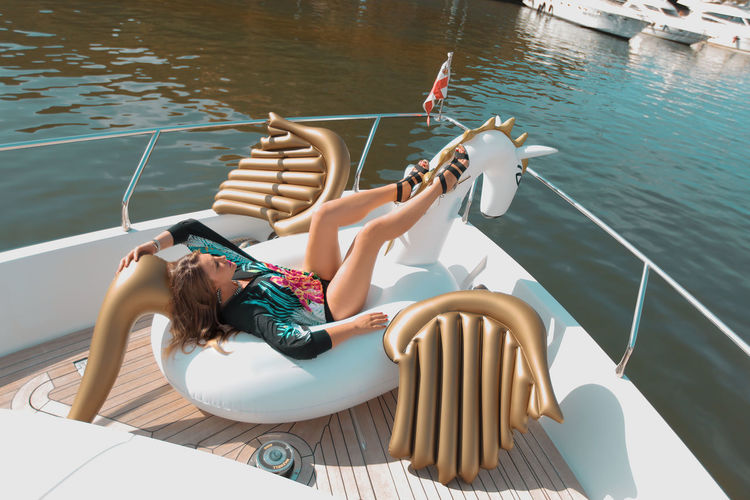 Young Woman Sitting On Inflatable Raft In Boat Over River