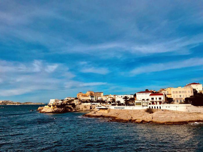 Buildings by sea against blue sky